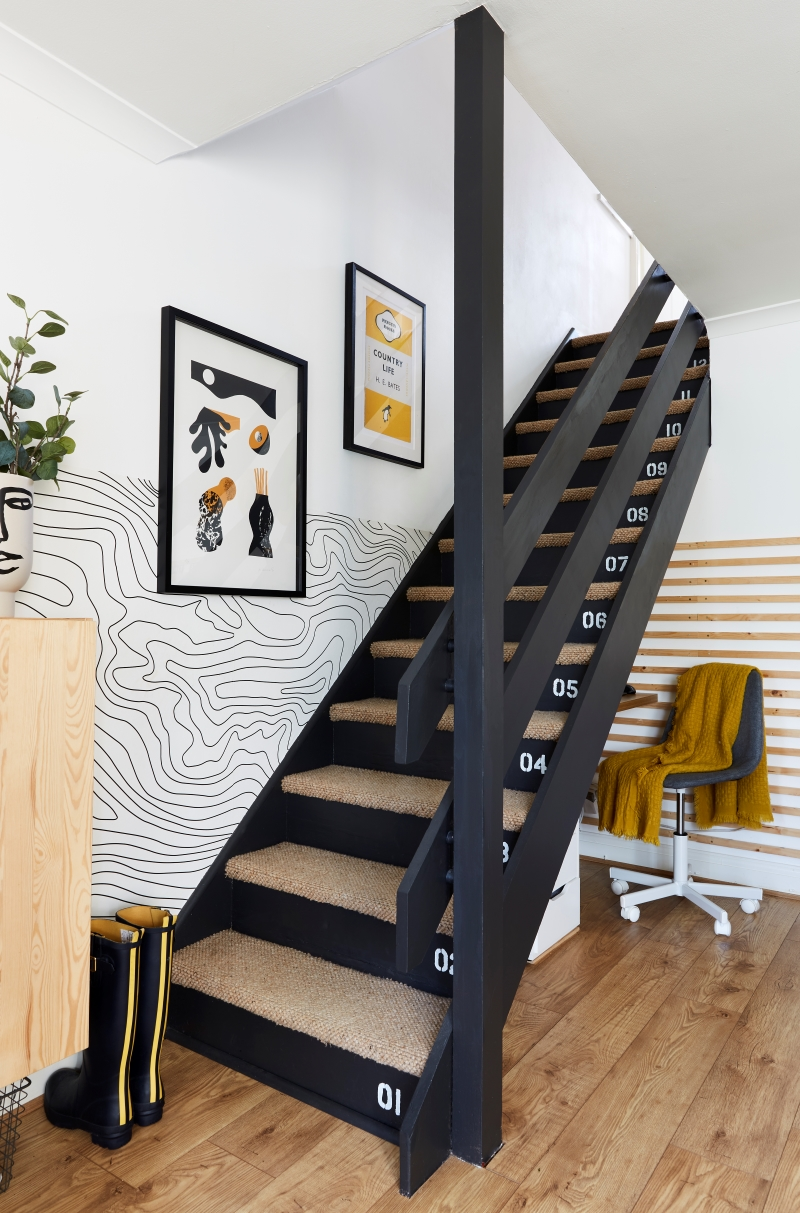 View of the painted black stairs in this multi-functional living room
