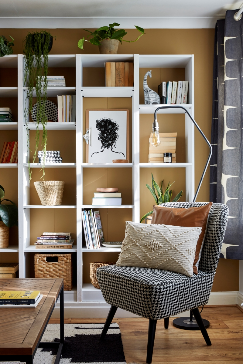 Dog tooth wing back chair in front of a wall to ceiling bookcase wall styled with books and images