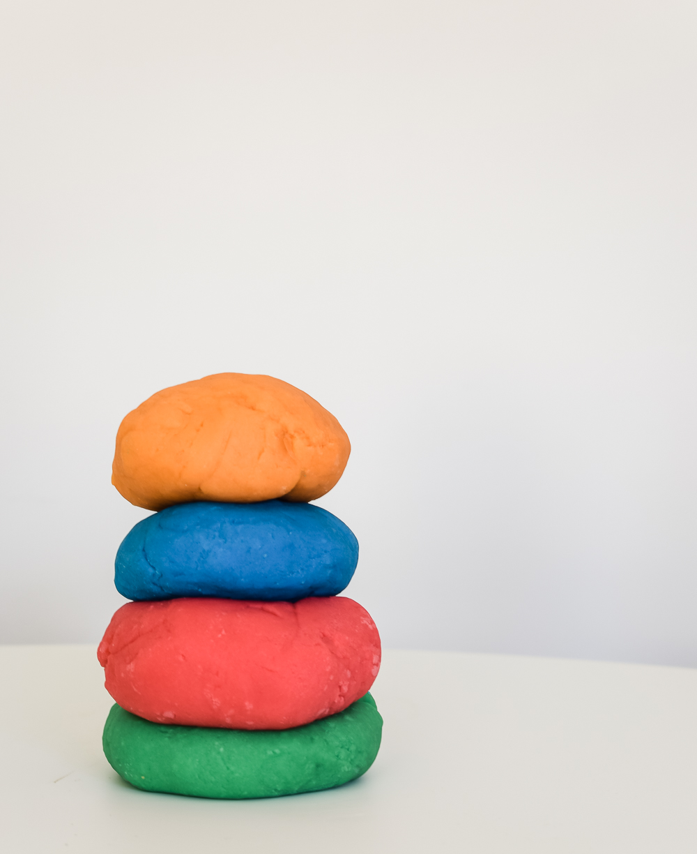 homemade playdough stacked on top of each other with a white background. Red, blue, orange and green