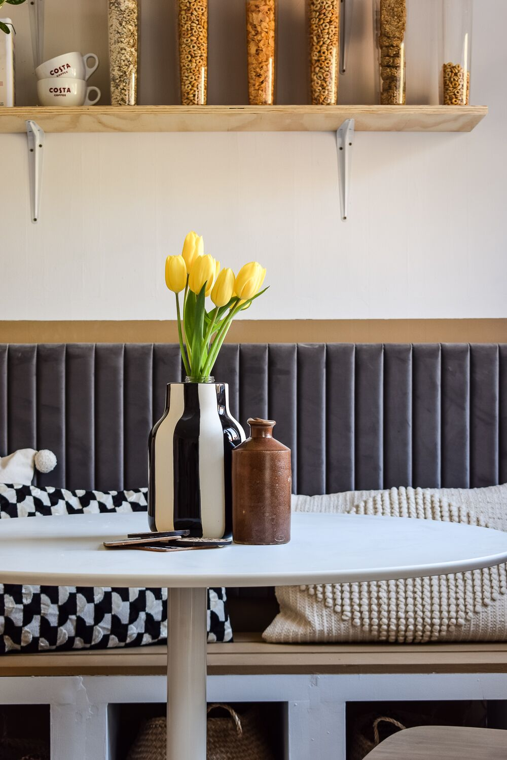Close up of grey velvet headboard behind bistro table