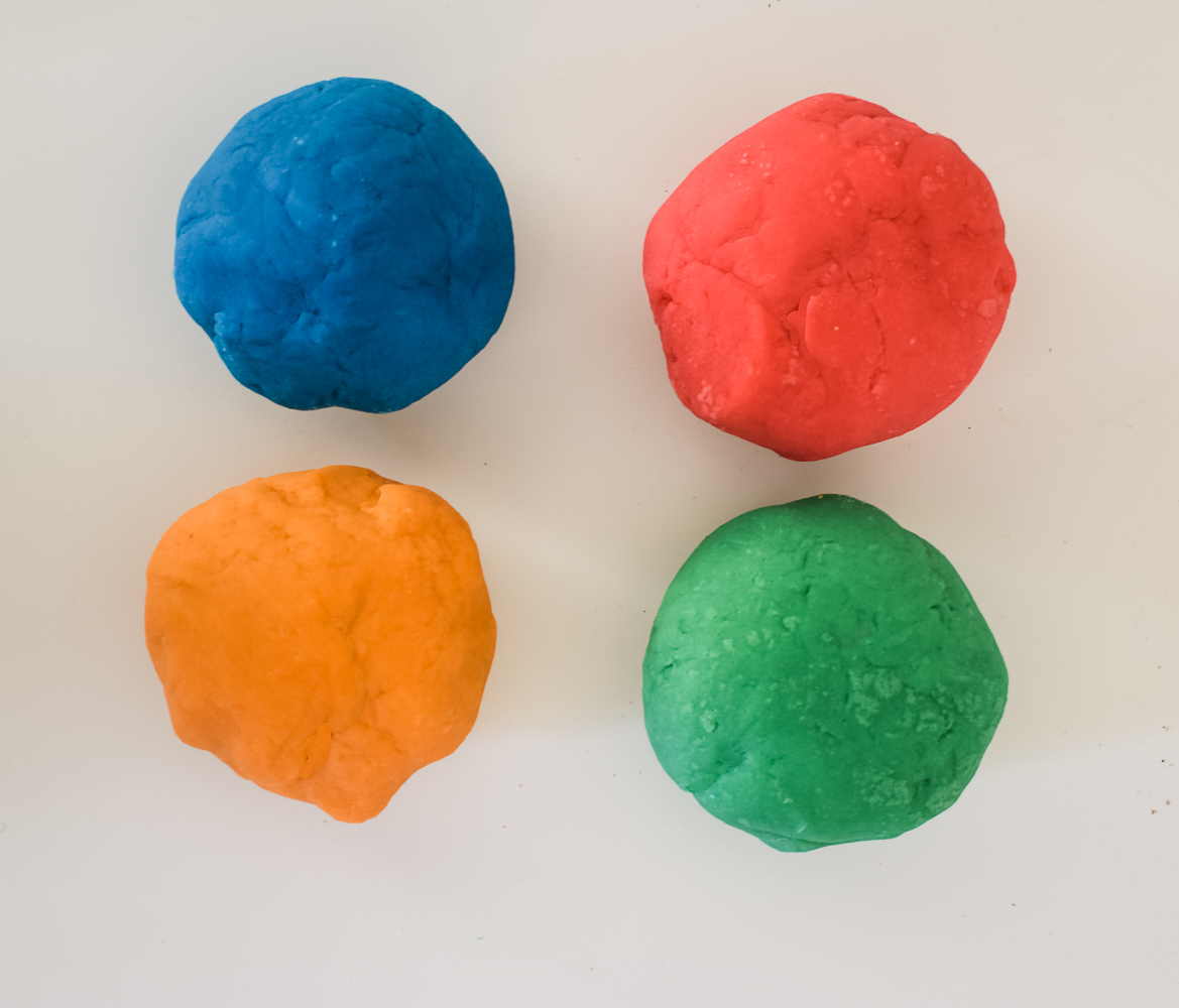 homemade playdough rolled into balls on a white background. Red, blue, orange and green