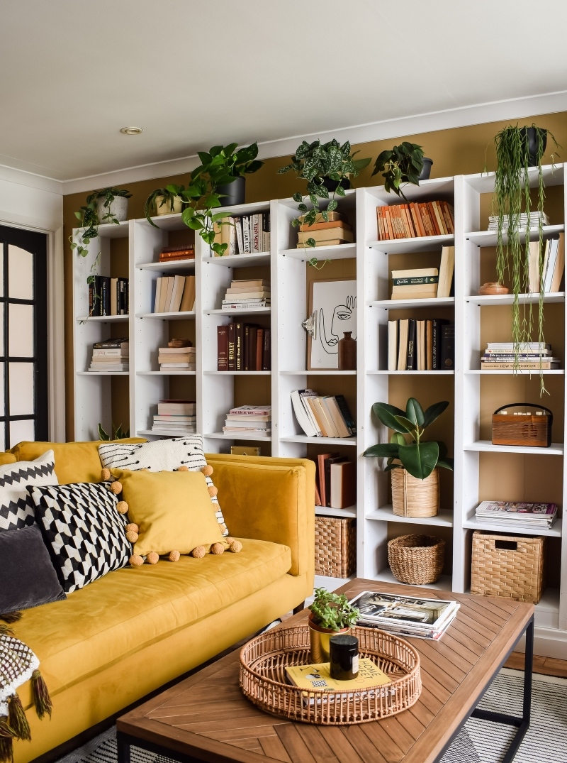 Yellow eden sofa at side angle view with wall to wall bookcases in place