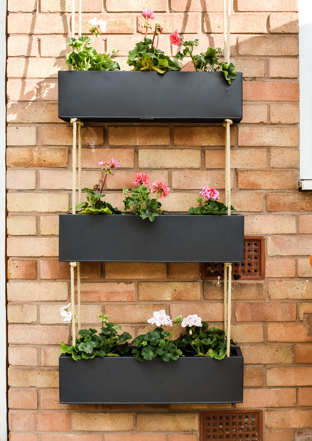 Black outdoor hanging basket on a brick wall