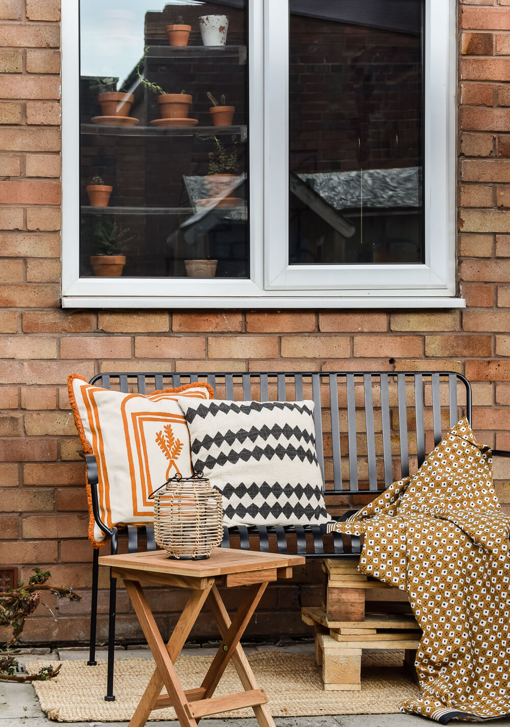 Image of garden furniture from habitat UK. Garden bench, table and cushion