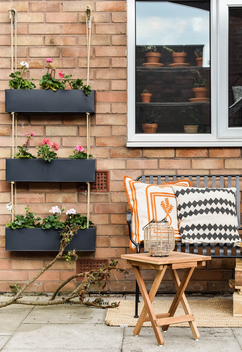 Black outdoor hanging planter on a brick wall in the garden