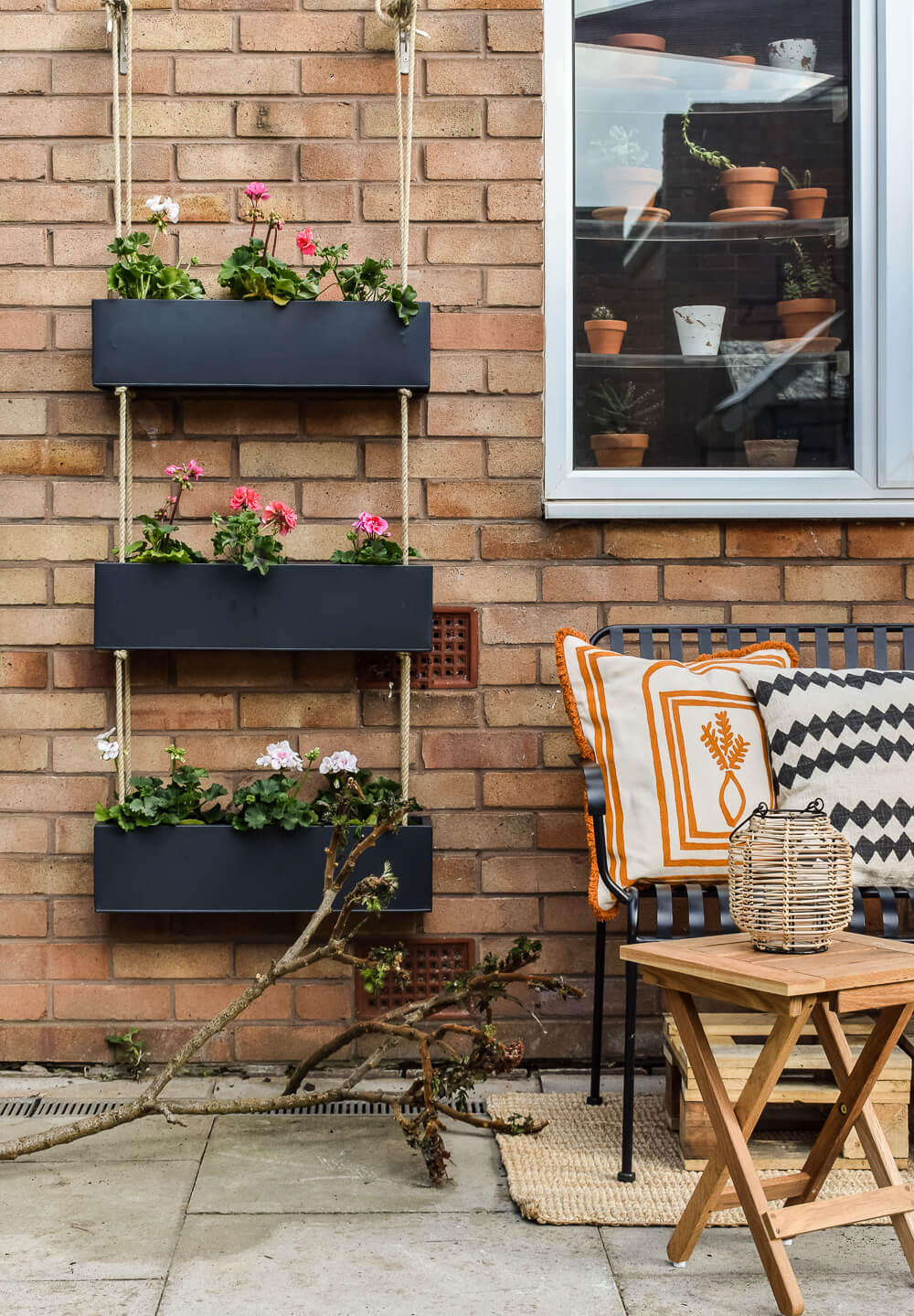 Black outdoor hanging planter against brick wall next to metal bench