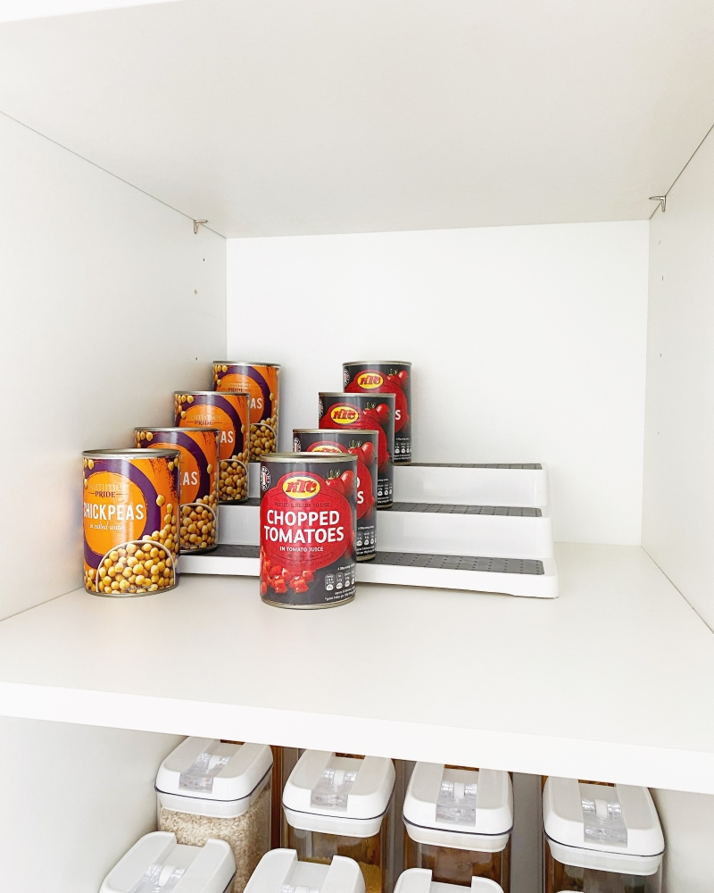 Tinned can of tomatoes on tiered organiser in cupboard