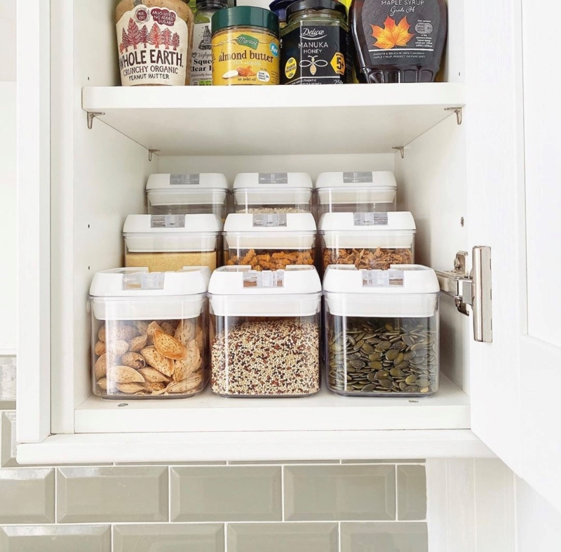 Plastic airtight storage containers lined next to each other in kitchen cupboard
