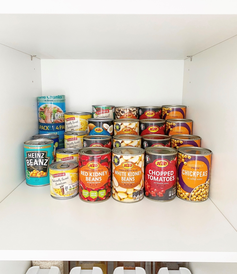 Tinned can of tomatoes, beans and kidney on tiered organiser in cupboard