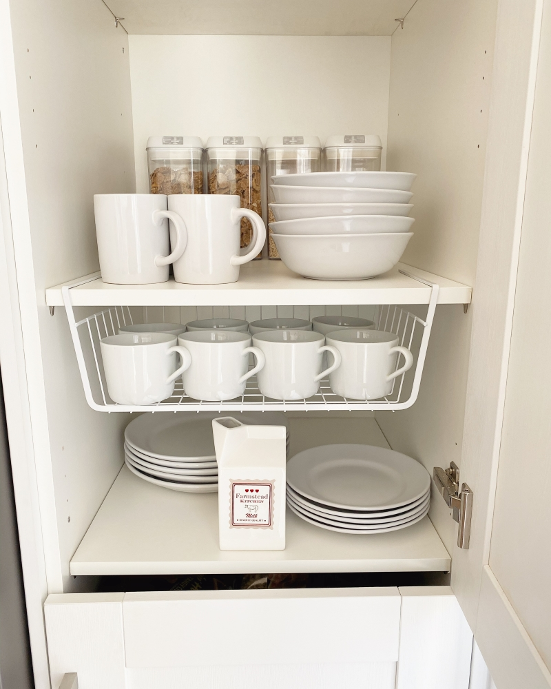 Organised kitchen pantry with cups, bowel and under shelf storage basket