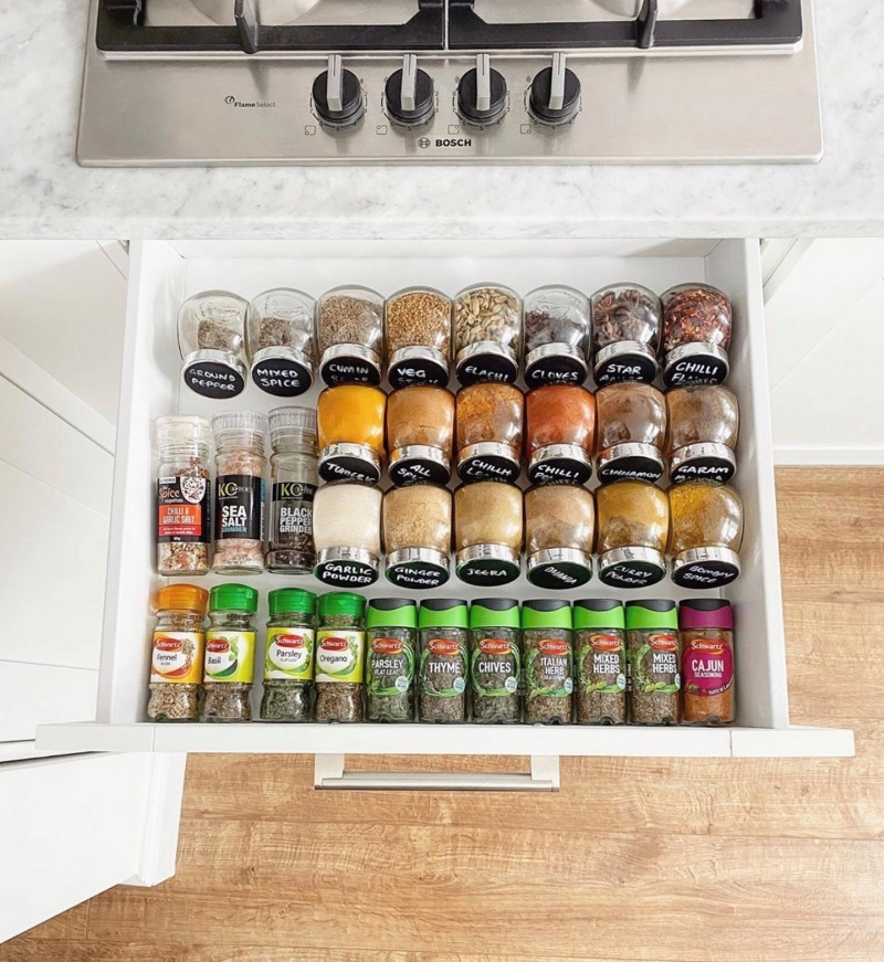 IKEA spice jars filled with spices in a drawer in three rows