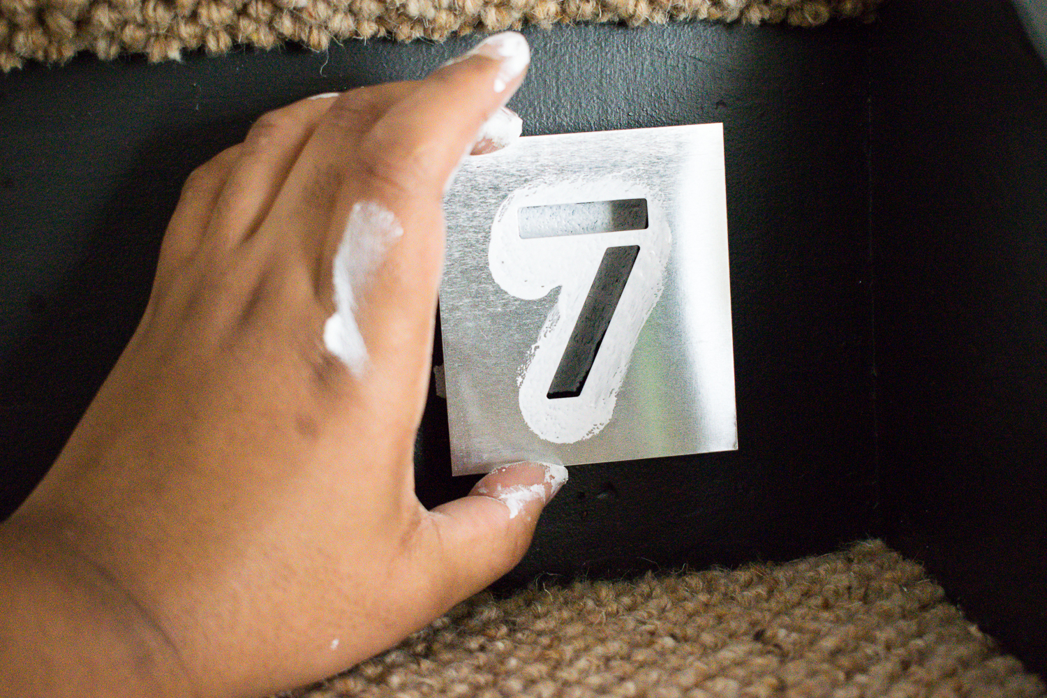 Image of me holding number 7 stencil on stairs
