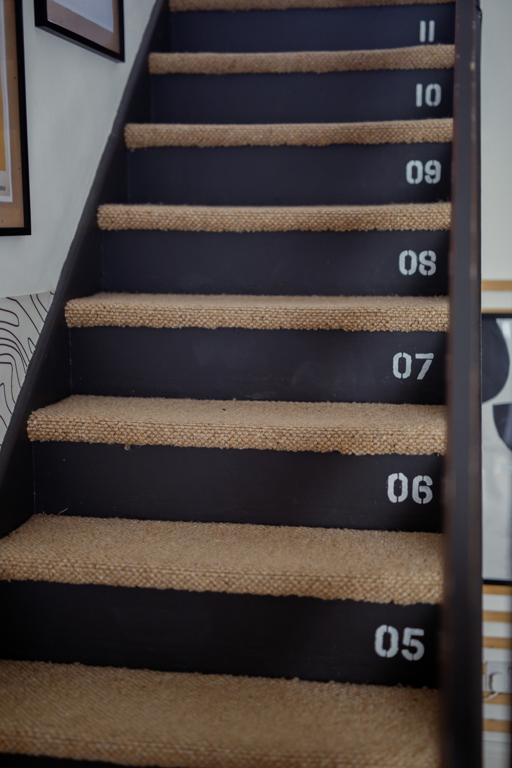 Image of painted black stairs with stenciled numbers
