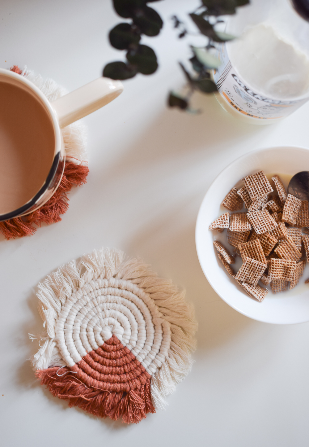 MACRAME COASTERS ON A WHITE TABLE NEXT TO A BOWL OF CEREAL