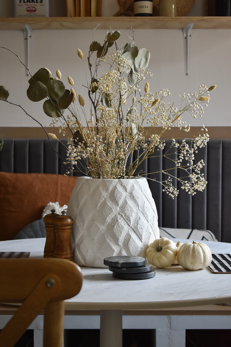 Close up of the diy marble table. A textured vase is atop the table and filled with dried flowers and leaves. White mini pumpkins are next to the vase.