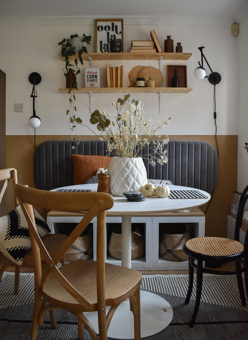 Dining nook with neutral half painted wall and a grey headboard. A diy marble table in the middle with two wooden cafe style chairs. 2 x black wall lights and styled plywood shelving above the seating on the part of the wall that is painted white.