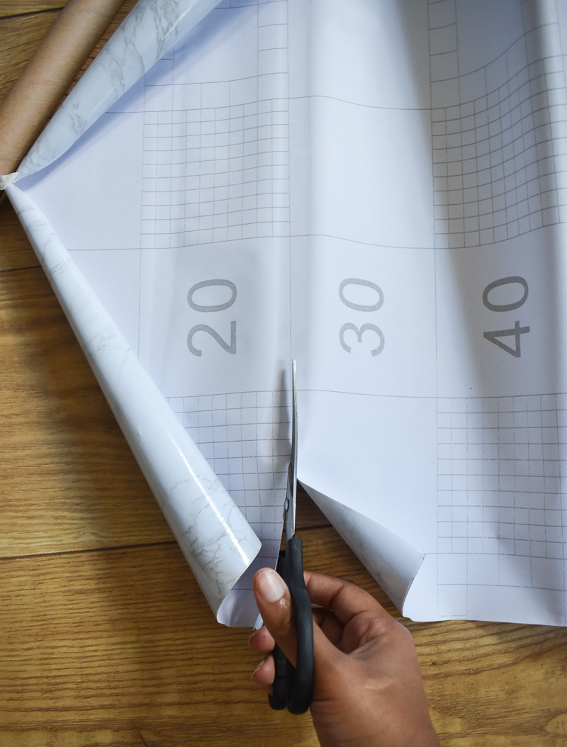 Cutting the contact paper with black scissors