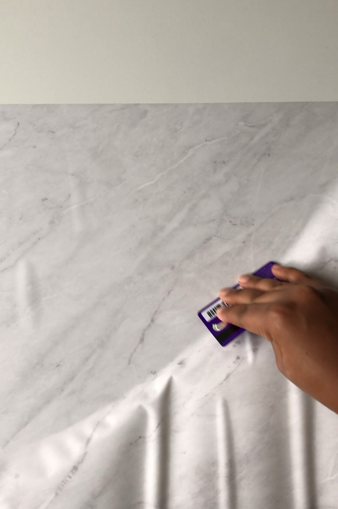 Medina smoothing the marble contact paper on to the table using a purple card