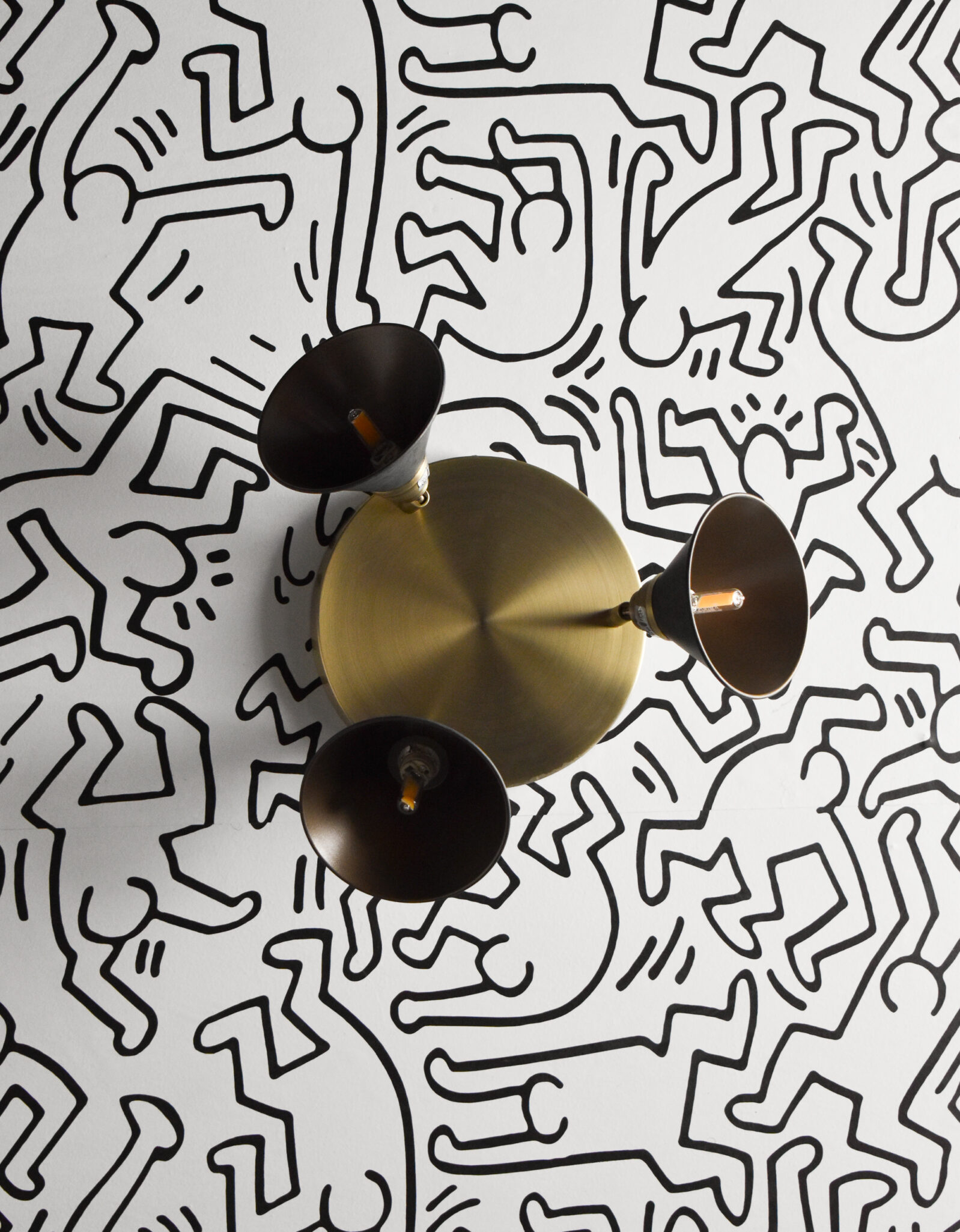 Keith haring monochrome self-adhesive wallpaper and brass lighting fixture