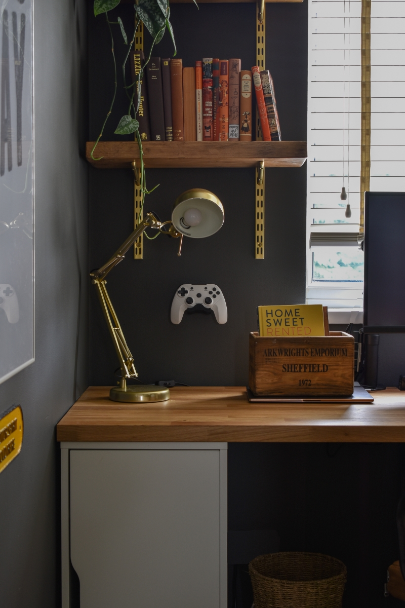 bespoke wooden desk for cool man cave office with dark walls and brass fittings