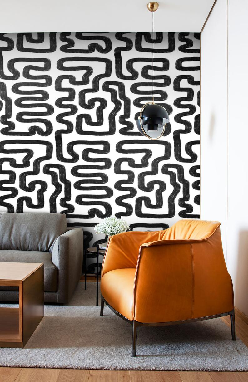 living room geometric abstract monochrome self-adhesive wallpaper with brass lighting and leather accent chair