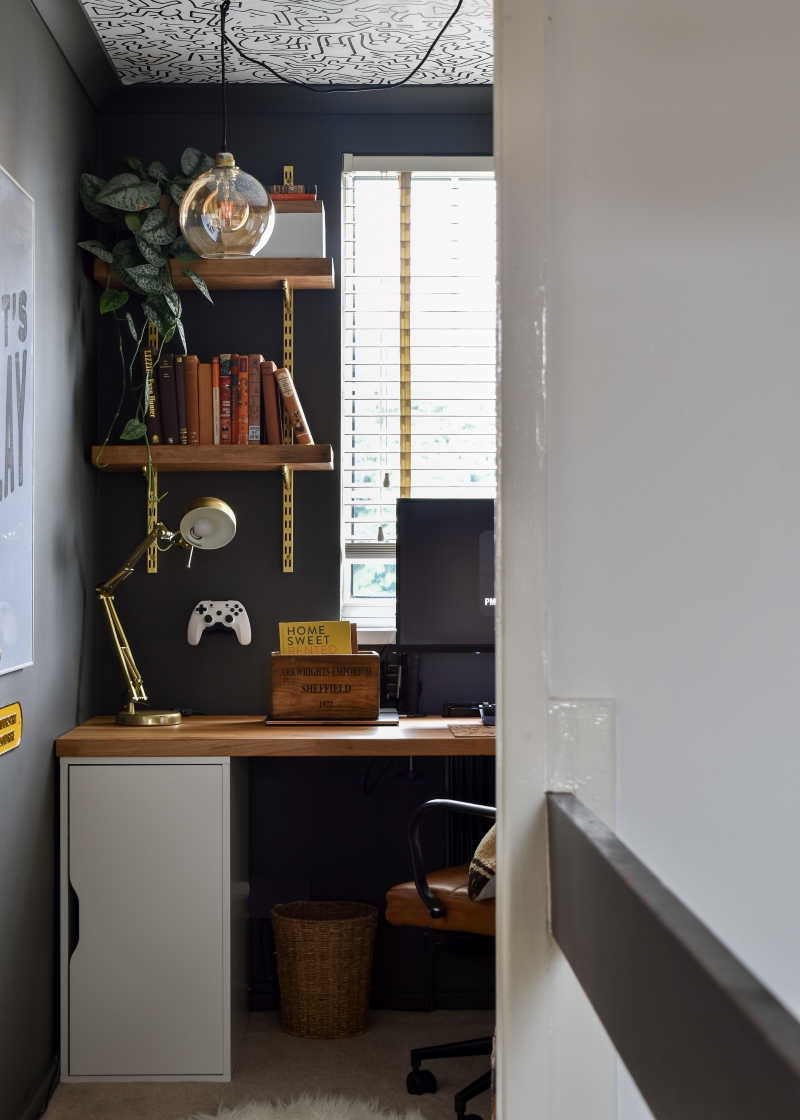 After shot man cave office with dark wall colour brass fixtures and monochrome self-adhesive wallpaper