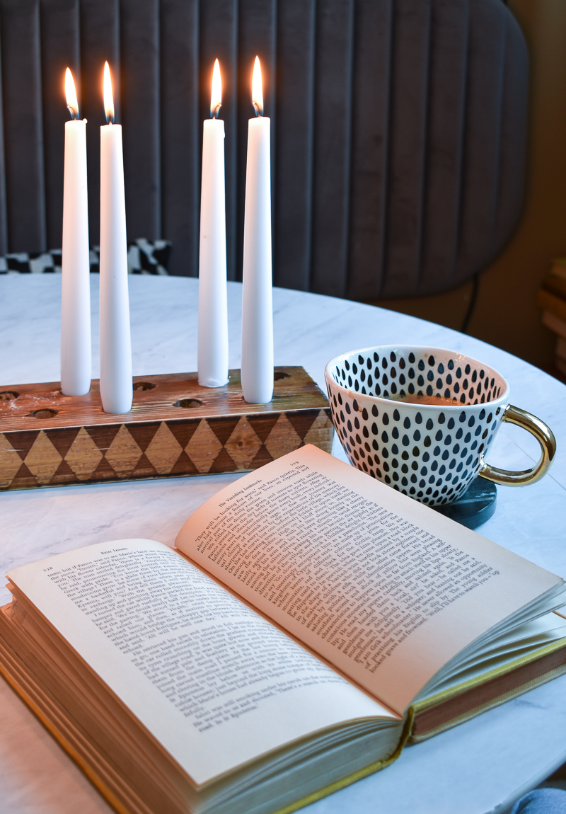 Close up of checkered candlestick holder next to book on table