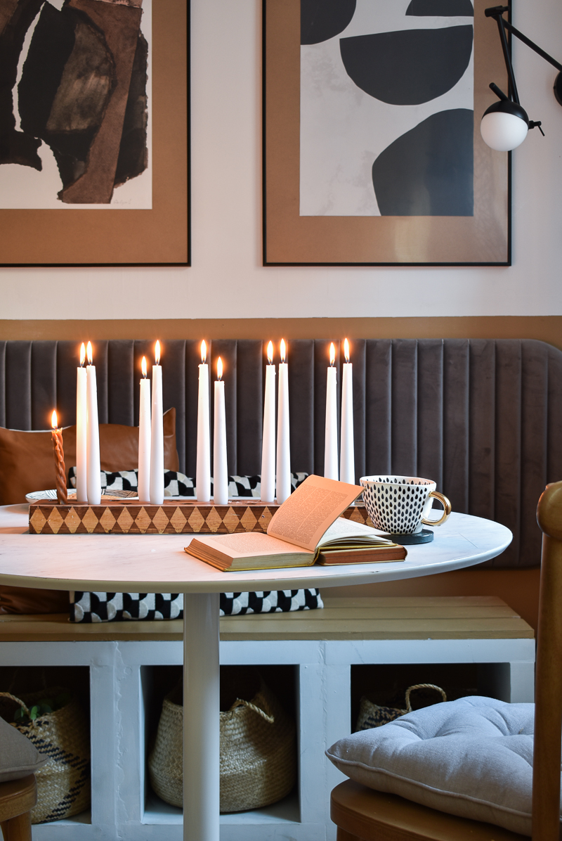 Checkered candle stick holder on round table with white candles inserted that are lit