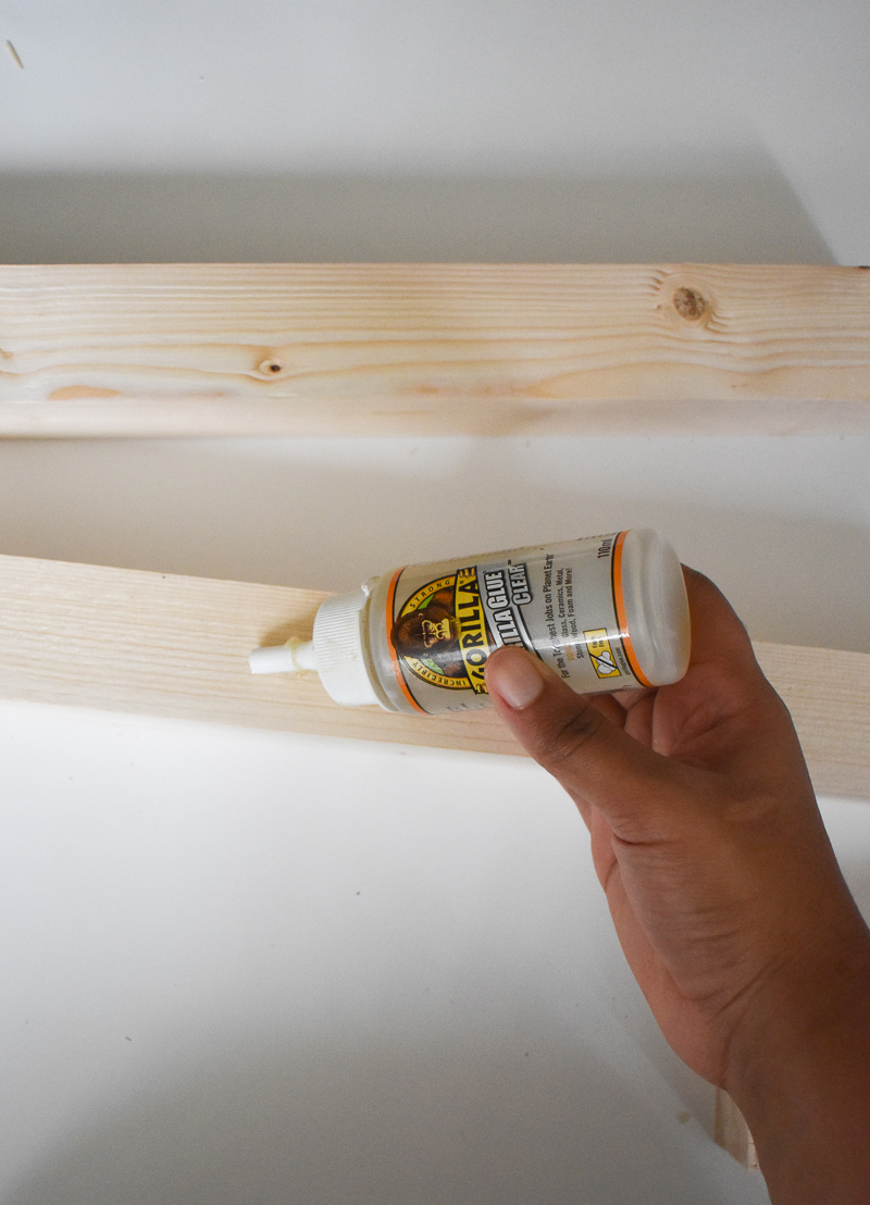 Applying clear wood glue to one side of the the wood length
