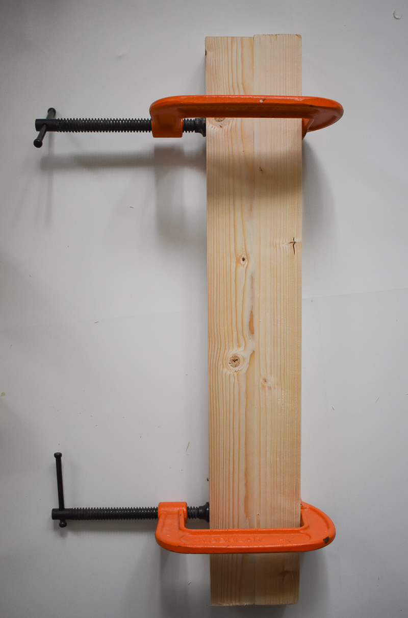 2 pieces of wood held together with metal orange clamps