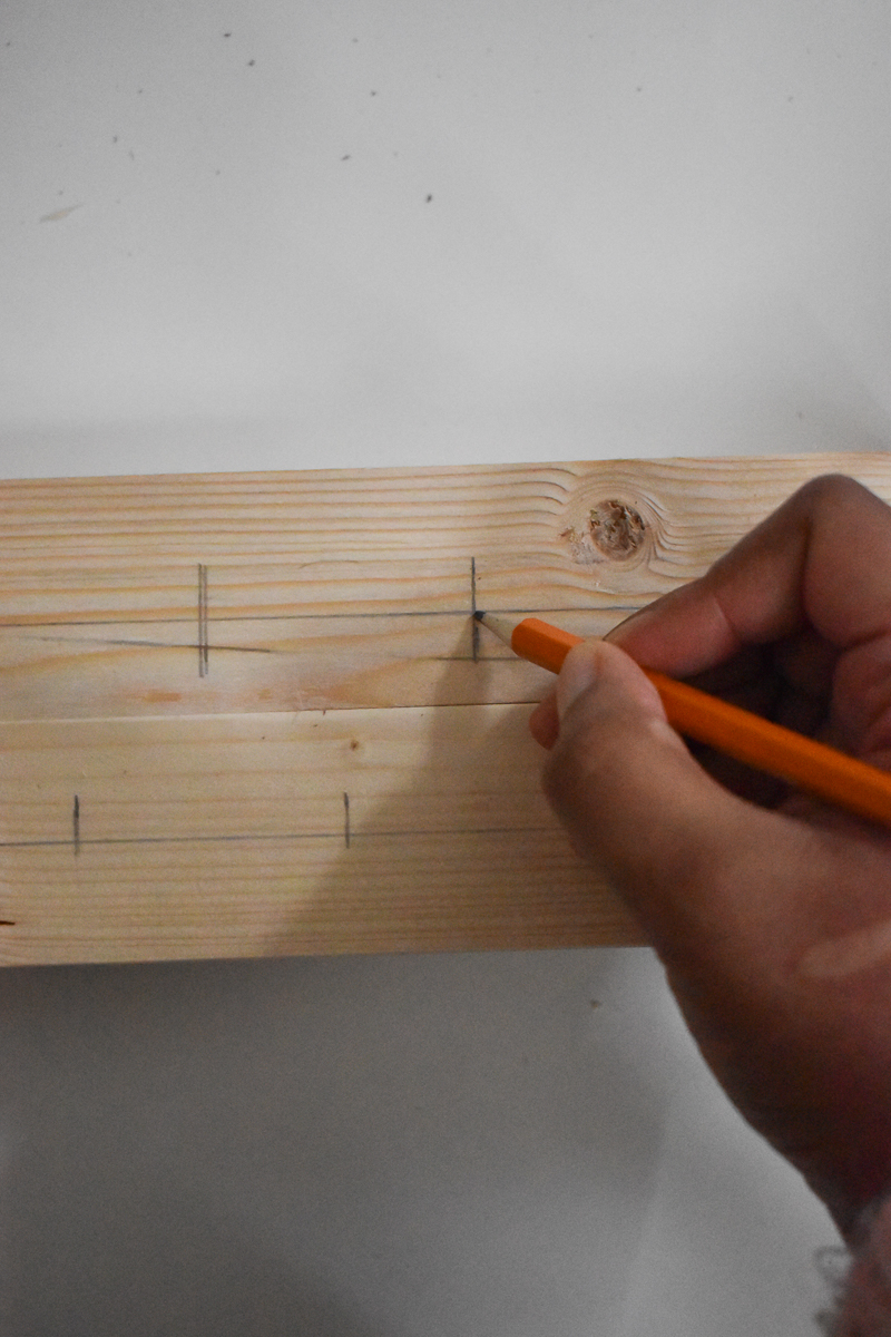 Using a pencil to mark out positions on the candle stick holder.