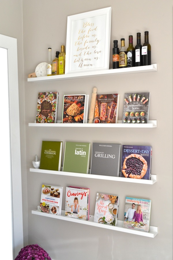 Cookbooks and kitchen items stored on picture ledges in a kitchen.