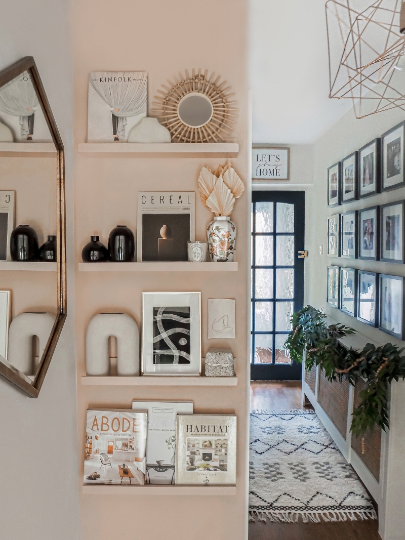 Narrow wall painted blush with matching picture ledges displaying art and pottery pieces in an entry way