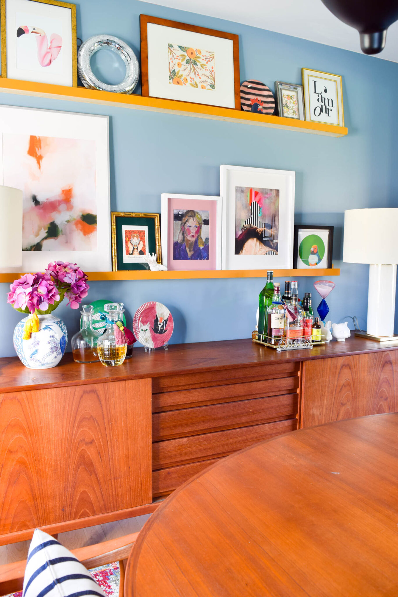 Bright modern artwork on yellow picture ledges above a danish modern buffet in the dining room.
