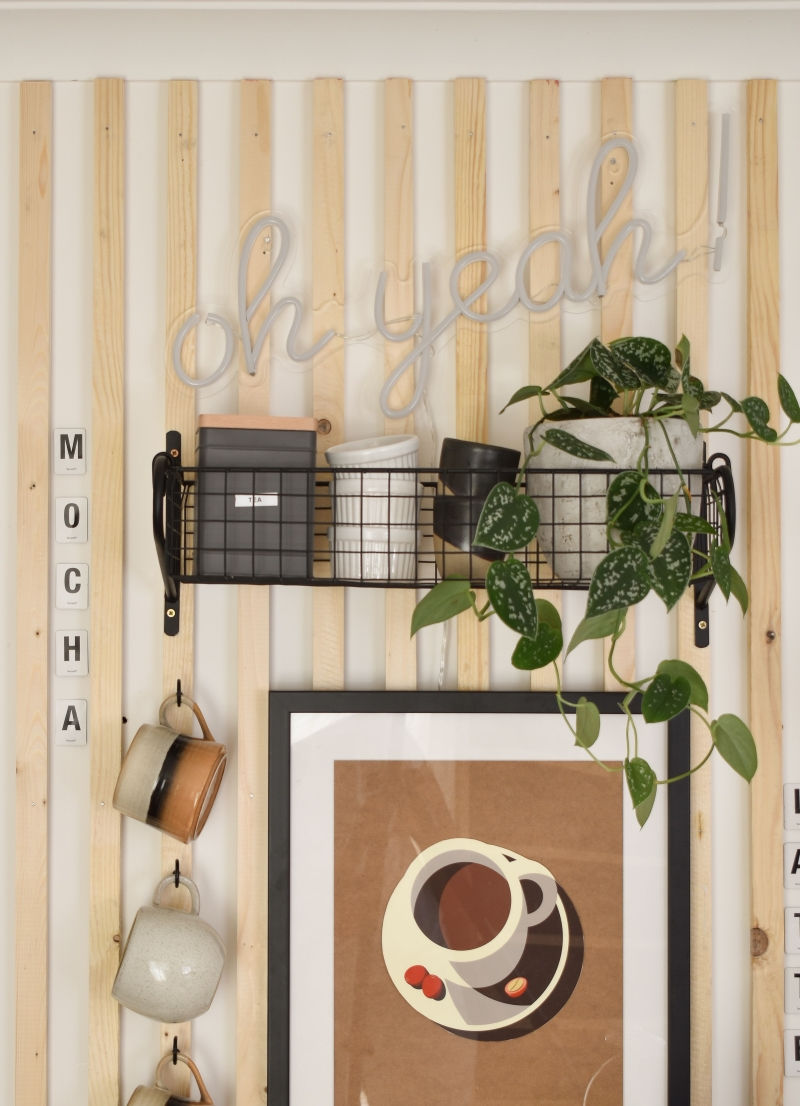 close up diy coffee station cups on hooks and basket shelf with storage canisters and neon wall art