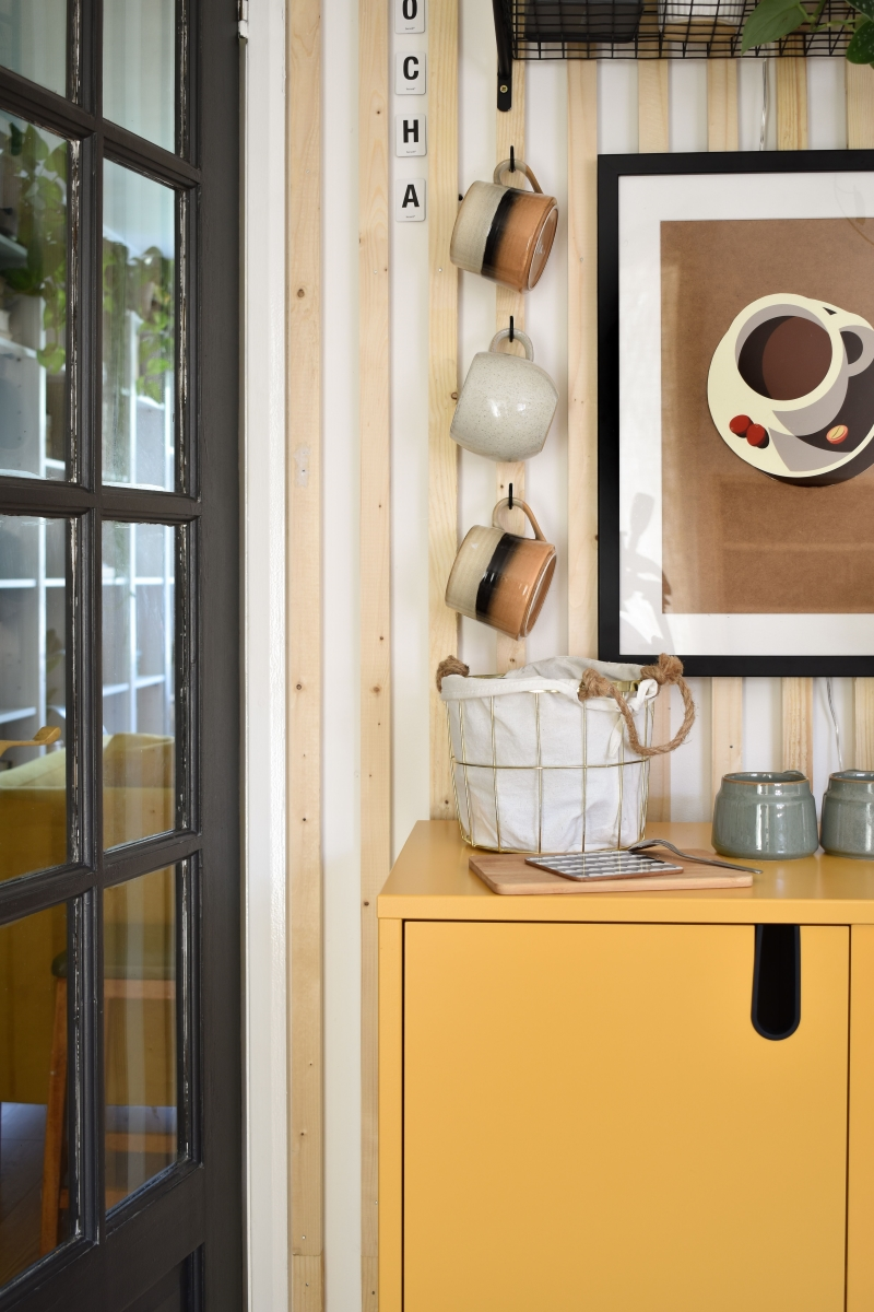 close up diy coffee station with yellow cabinet stoneware cups on hooks and storage basket with neutral coffee cup wall art