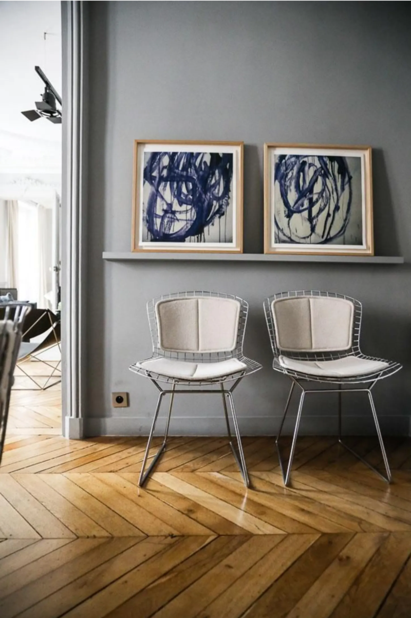 Navy blue modern art on a gray picture ledge above two wire chairs