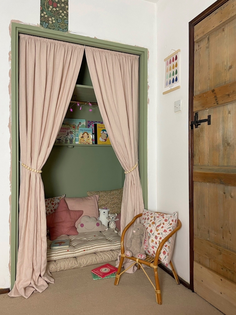A closet with doors removed, painted green. A picture ledge holds books over a cushion to create a hidden reading nook.