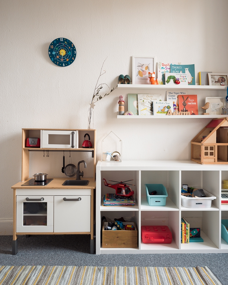 Picture ledges over a cubby shelf. They hold photographs and children's books.