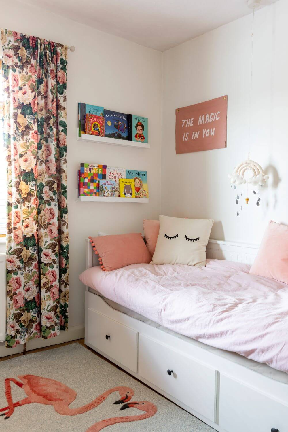 Daybed in front of picture ledges hung on the wall and lined with childrens books.