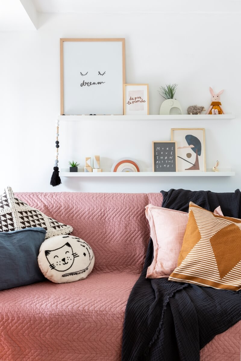 White picture ledges holding art and small toys over a pink daybed.