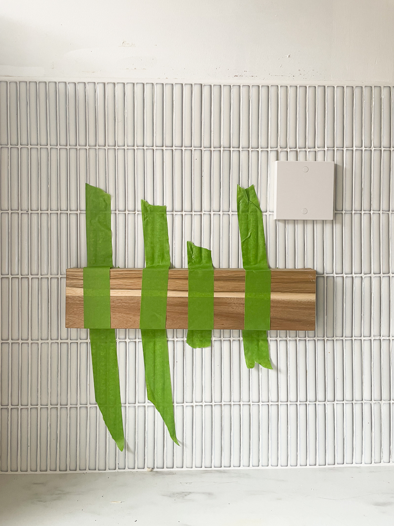 4 pieces of painters tape used to hold the magnetic wooden knife rack in place against the white kitkat tiles.