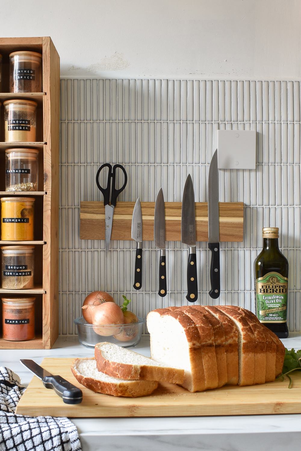 Wooden diy magnetic spice rack attacked to kit kat tiles. A loaf of bread on a chopping board in front of the knife rack on countertops,