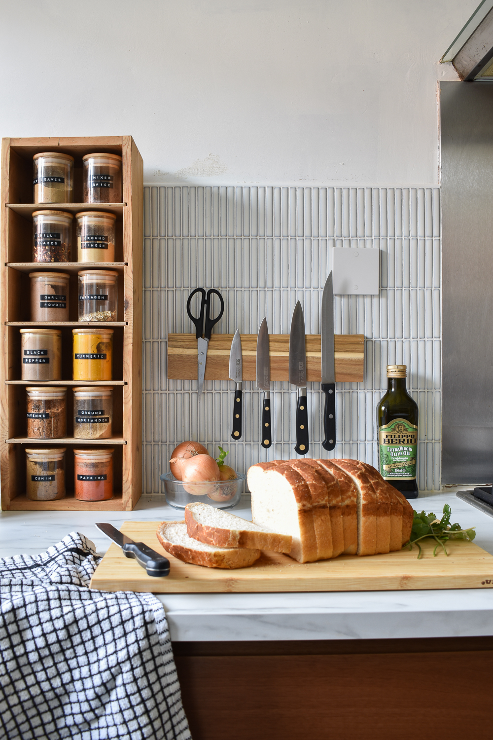 Wooden diy magnetic spice rack attached to kit kat tiles. A loaf of bread on a chopping board in front of the knife rack on countertops,
