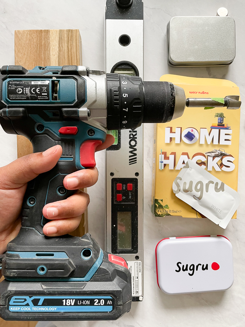 Tools needed. Pictured medina hand holding drill and drill bit over a flat lay of level, magnet, sugru kits and wood.