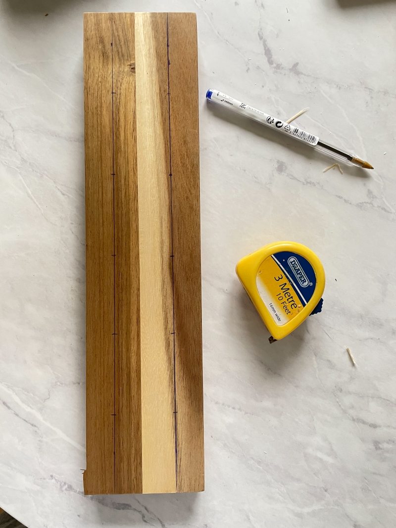 Wood laying on a marble surface with 10 points marked equally on it with blue biro pen. A tape measure can be seen/
